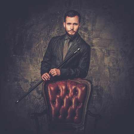Handsome well-dressed man with stick standing near leather chair  photo