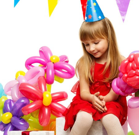 girl in red dress: Little girl in red dress sitting on gift boxes Stock Photo