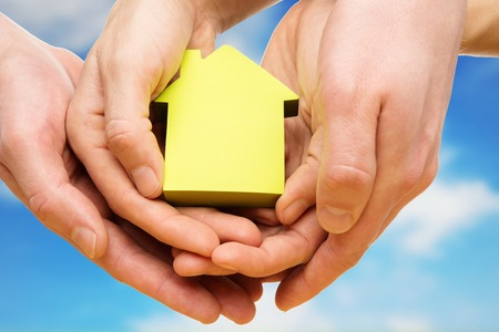 Man and woman hands holding conceptual paper house against blue sky photo