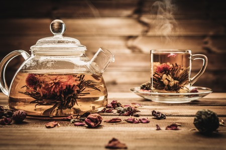 Teapot and glass cup with blooming tea flower inside against wooden background  photo