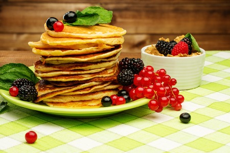 Healthy breakfast with pancakes, fresh berries and muesli on tablecloth in rural interior  photo