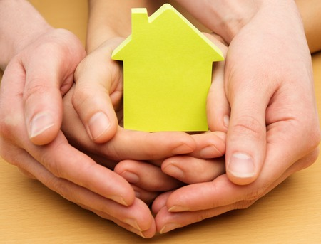 neighbourhood: Man and woman hands holding conceptual paper house  Stock Photo