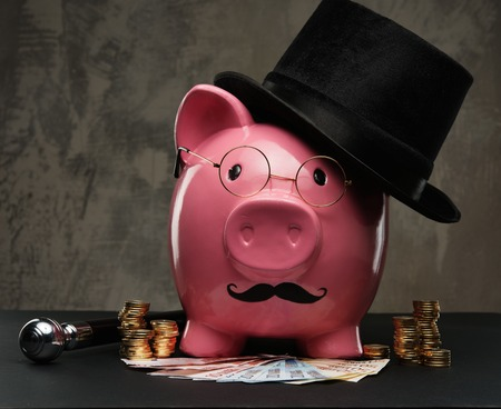 capitalist: Piggybank in glasses and hat with pile of coins and banknotes