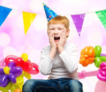 funny birthday: Funny little redhead boy among birthday balloons