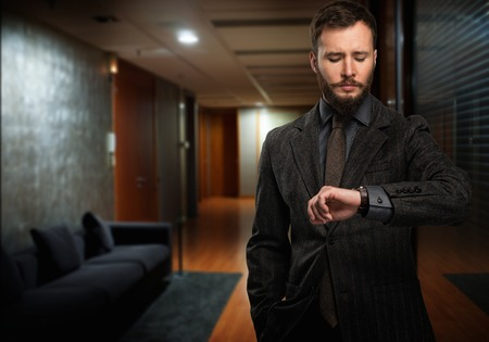 Handsome well-dressed man with beard looking at his wrist watch in a hallway photo