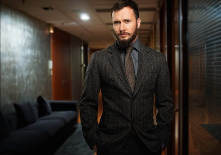 Handsome well-dressed man with beard in a hallway photo