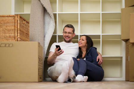 packing: Young positive couple  among boxes in their new home Stock Photo
