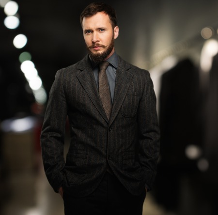 Handsome well-dressed man with beard in a clothing store