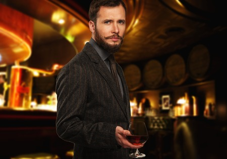 Handsome well-dressed man in jacket with glass of beverage in restaurant interior  photo