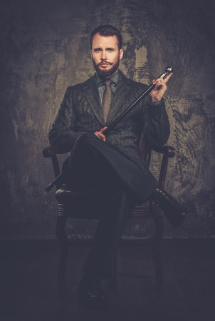 welldressed: Handsome well-dressed with stick sitting in leather chair  Stock Photo