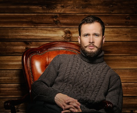 Handsome man wearing cardigan in wooden rural house interior  photo