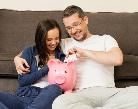 bank interior: Cheerful young couple putting banknote in piggybank
