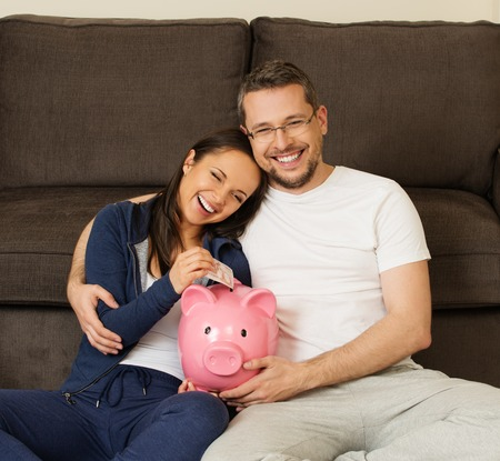 Cheerful young couple putting banknote in piggybank  photo
