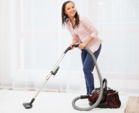 house cleaner: Young cheerful brunette woman vacuum cleaning carpet in home interior
