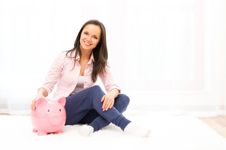 Cheerful young woman sitting on a carpet with piggybank photo