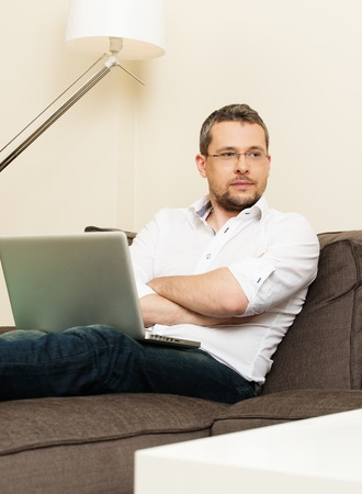 fray: Young man with fray hair with laptop on sofa in home interior  Stock Photo