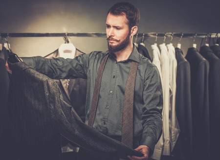 choosing clothes: Handsome man with beard choosing jacket in a shop