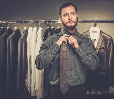Handsome man with beard tying a tie in a clothing store photo
