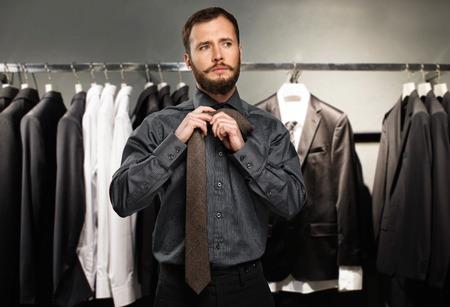 gamme de produit: Bel homme � la barbe attachant une cravate dans un magasin de v�tements Banque d'images