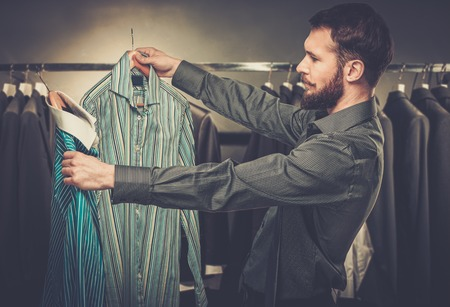 Handsome man with beard choosing shirt in a shop photo