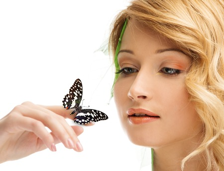 Dreaming young woman in conceptual spring costume with butterfly on her hand  photo