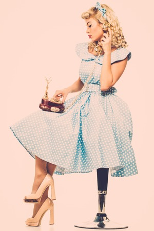 Coquette blond pin up style young woman in blue dress with vintage phone  photo