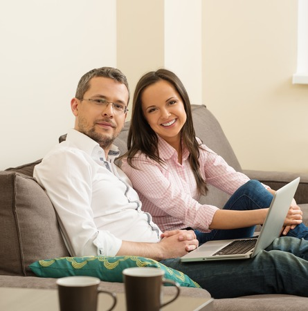 inet: Young cheerful couple with laptop on a sofa in home interior