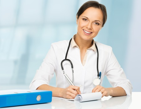 Young positive brunette doctor woman behind table taking notes photo