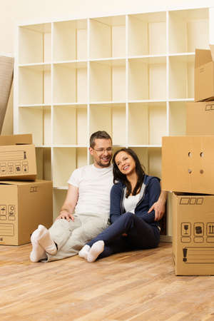 Young positive couple  among boxes in their new home photo