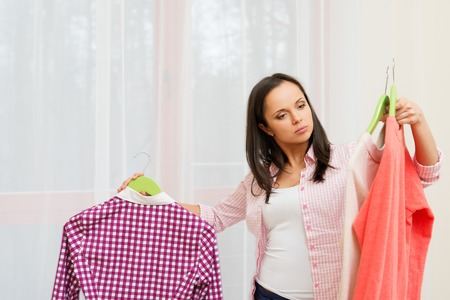 Young brunette woman choosing clothes in home interior  photo