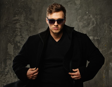Stylish young man in black coat and sunglasses photo
