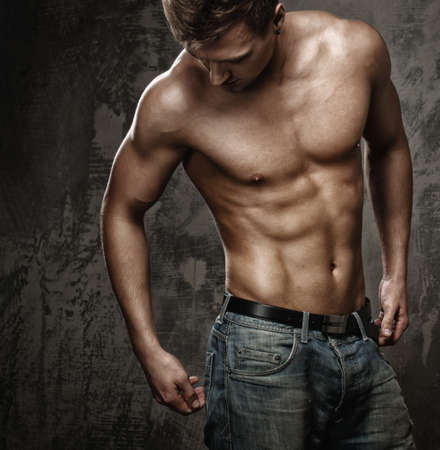 muscular man: Young man with muscular  body in blue jeans