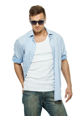 Stylish man in blue shirt and jeans wearing sunglasses isolated on white photo