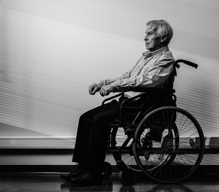Thoughtful senior man in wheelchair in nursing home  photo