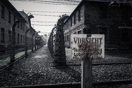 Electric fence and warning sign in former Nazi concentration camp Auschwitz I, Poland photo