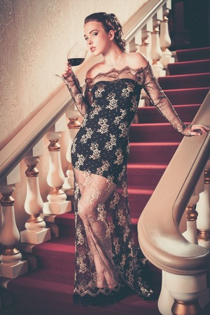 Beautiful young woman in long evening dress with glass of red wine standing on a steps in luxury interior  photo