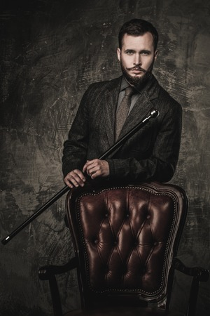 Handsome well-dressed man with stick standing near leather chair  Stock Photo - 27447158
