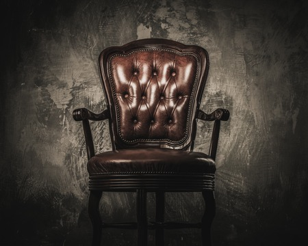 antique furniture: Comfortable wooden chair against concrete wall Stock Photo