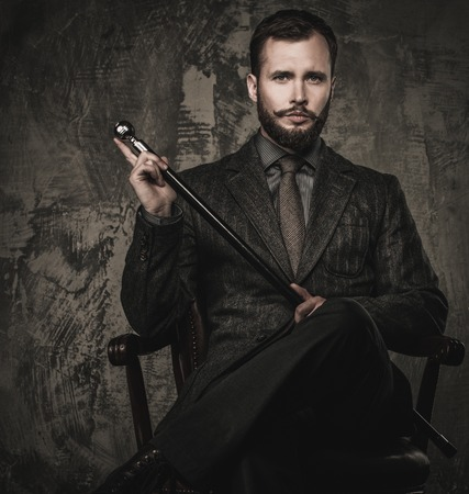 Handsome well-dressed with stick sitting in leather chair Stock Photo - 27447161