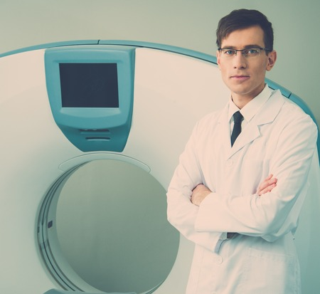 Young doctor standing near computed tomography scanner in a hospital photo