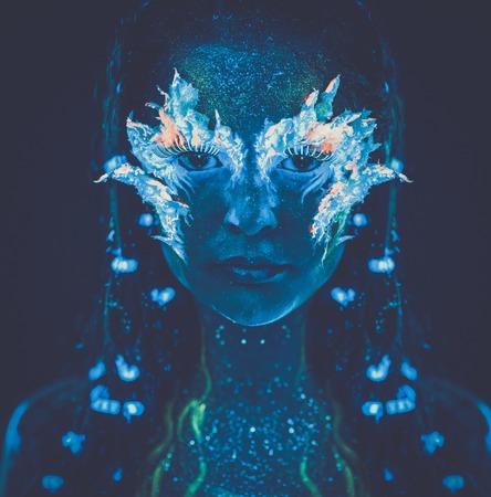 maquillaje de fantasia: Retrato de mujer hermosa con el arte del cuerpo que brilla intensamente en luz ultravioleta Foto de archivo