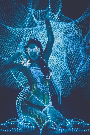 adult mermaid: Beautiful woman with body art glowing in ultraviolet light and freezelight background