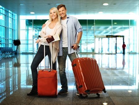 parejas de jovenes: Pareja feliz con maletas y un mapa en el aeropuerto Foto de archivo