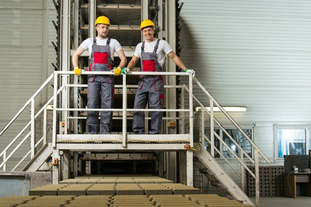 Two men in a safety hats on a factory   Stock Photo - 27655481