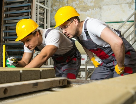 safety check: Worker and foreman in a safety hats performing quality check on a factory
