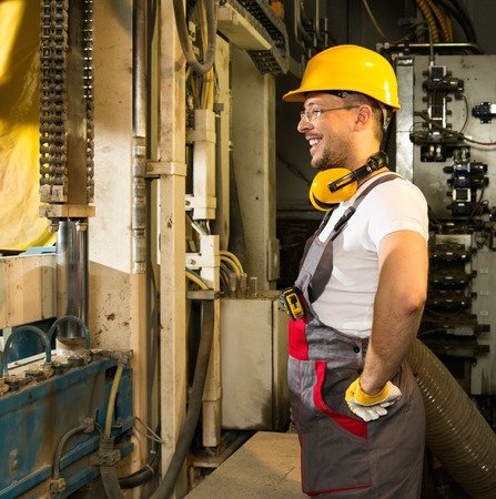 Cheerful worker in safety hat near machine on a factory Stock Photo - 27663919