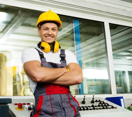Happy worker wearing safety hat in a factory control room photo
