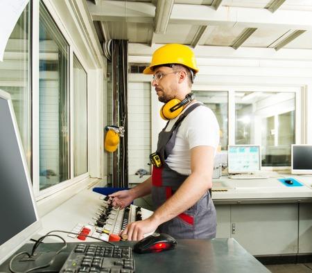 control de calidad: Operador que desgasta el sombrero de seguridad en una sala de control de la f�brica