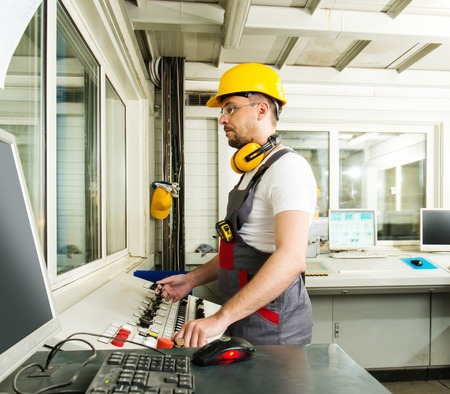 quality work: Operator wearing safety hat in a factory control room