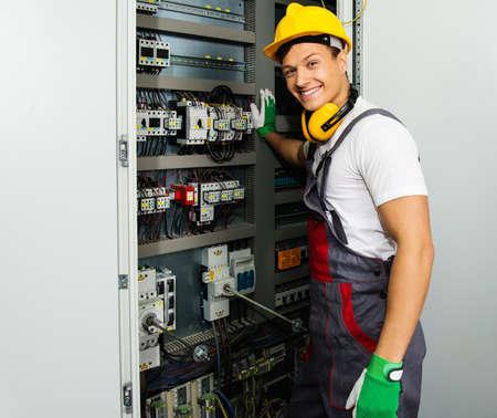 tablero de control: Electricista alegre en un sombrero de seguridad en una fábrica Foto de archivo
